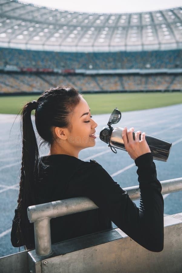 Jong sportvrouw drinkwater van sportenfles op stadion stock afbeeldingen