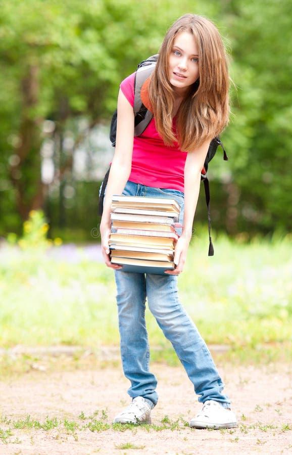 Jong studentenmeisje dat grote stapel van zware boeken houdt stock afbeeldingen