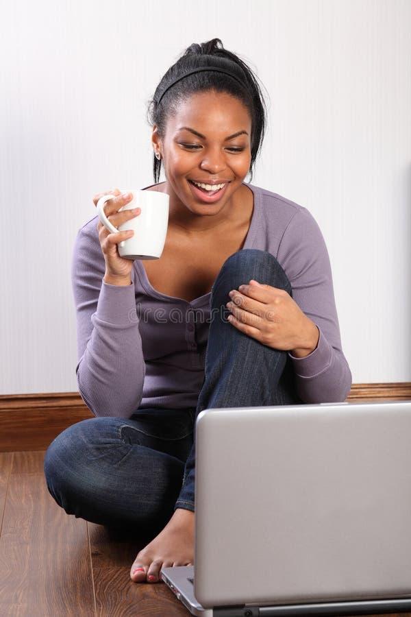 Jong studentenmeisje dat thuis laptop online met behulp van stock foto's