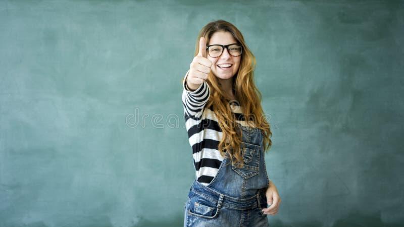 Jong studentenmeisje die duimen op groen bord tonen royalty-vrije stock afbeelding