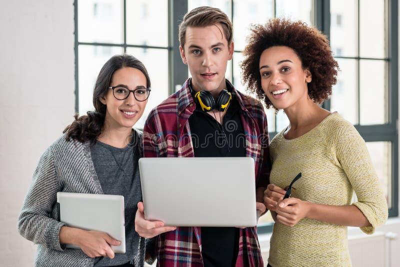 Jong team die over een bedrijfspresentatie op laptop in kijken stock afbeelding