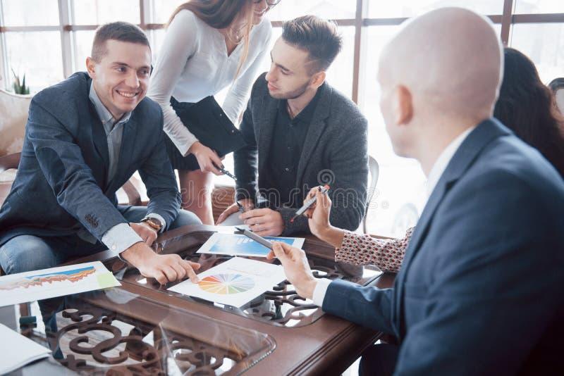 Jong team van medewerkers die grote bedrijfsbespreking in modern coworking bureau maken Het concept van groepswerkmensen stock fotografie