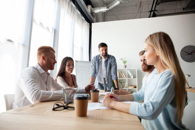 Jong team van medewerkers die grote bedrijfsbespreking in modern coworking bureau maken Het concept van groepswerkmensen stock afbeelding