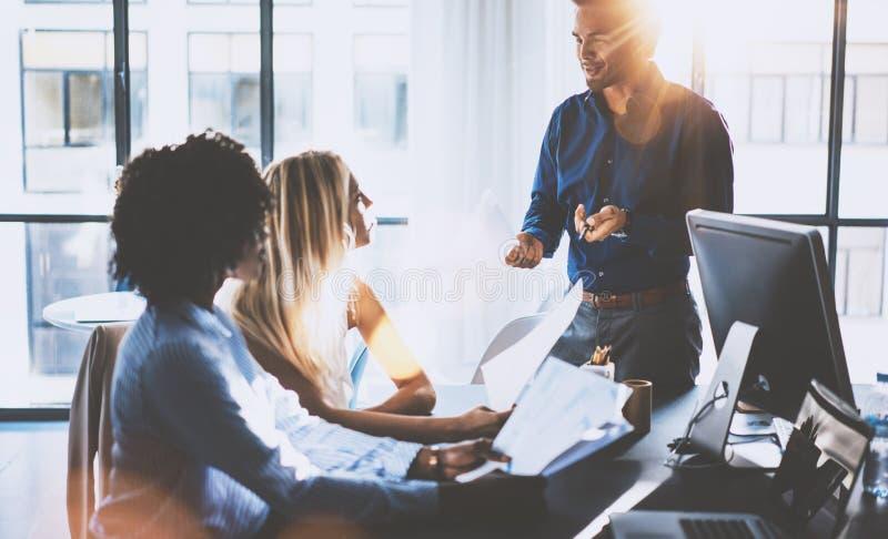 Jong team van medewerkers die grote vergaderingsbespreking in modern coworking bureau maken Spaanse zakenman die met twee spreken stock foto's