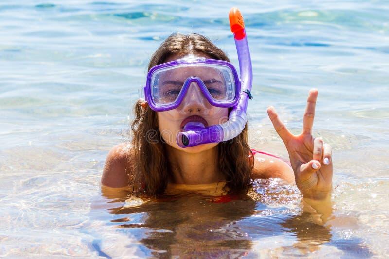 Jong tienermeisje bij de kust die een het duiken masker dragen stock foto