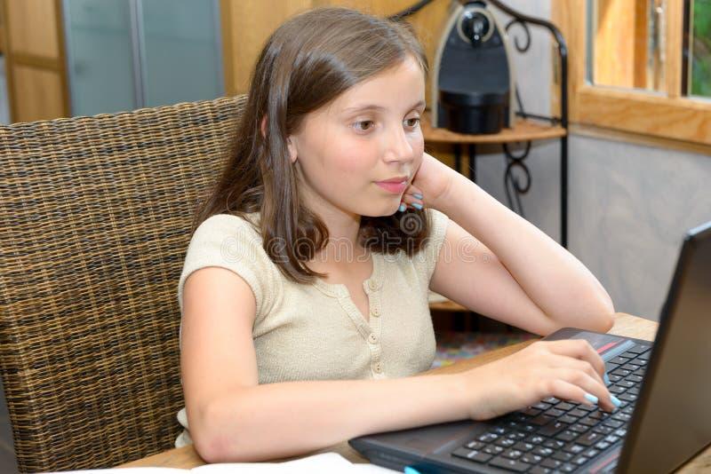 Jong tienermeisje die haar thuiswerk met laptop doen stock foto's