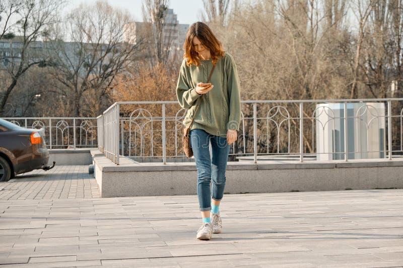 Jong tienermeisje die met telefoon lopen, die sms-bericht op smartphone, achtergrond van de de lente de zonnige dag lezen stock foto