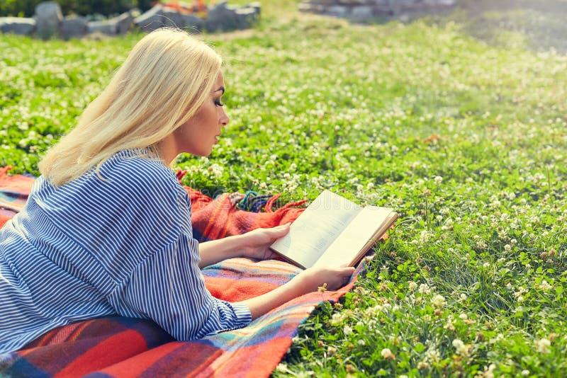 Jong tienermeisje gelezen boek en studiethuiswerk openlucht stock afbeeldingen