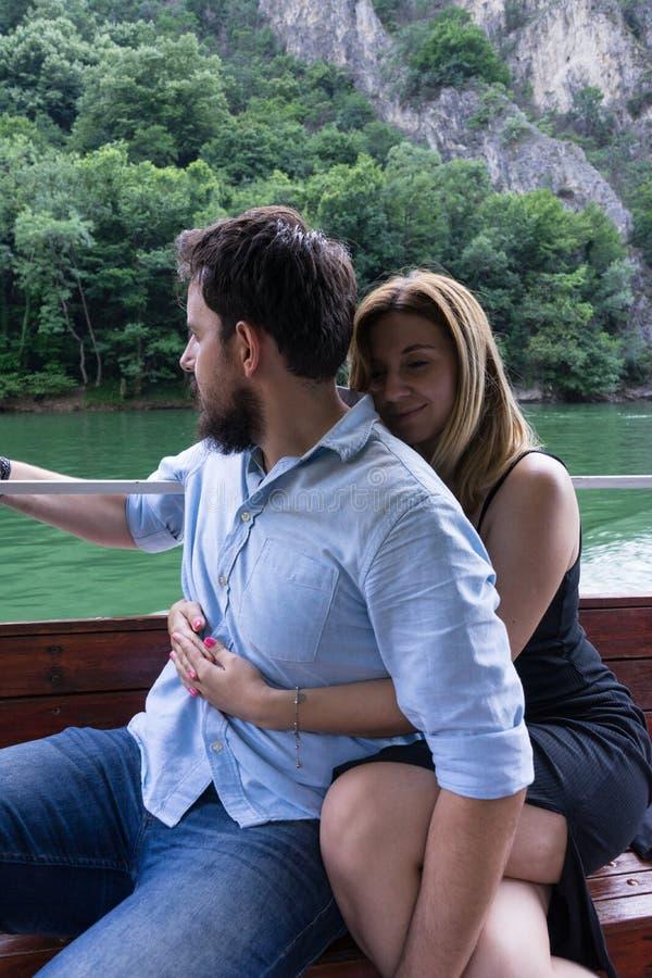 Jong toeristenpaar die in een kleine houten boot in een activiteit in de rivier koesteren Meisjesomhelzing een jongen met zwarte  royalty-vrije stock foto's