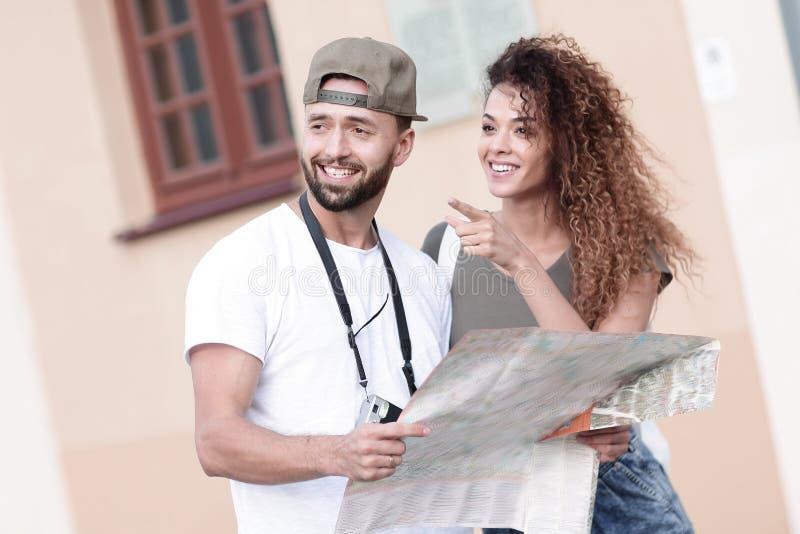 Jong toeristenpaar die met kaart een manier zoeken stock foto
