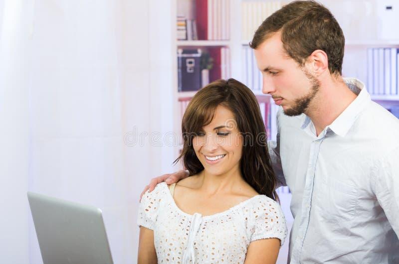 Jong toevallig aantrekkelijk paar die laptop met behulp van royalty-vrije stock foto
