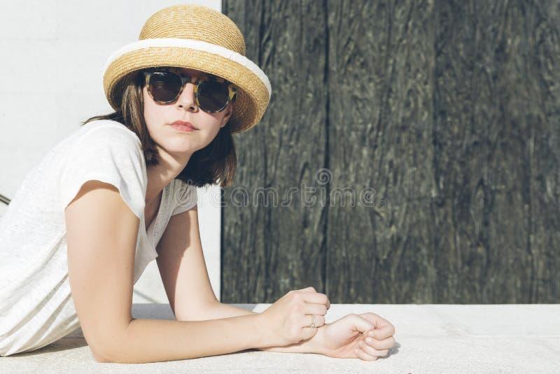 Jong toevallig meisje die een hoed en zonnebril dragen royalty-vrije stock afbeelding