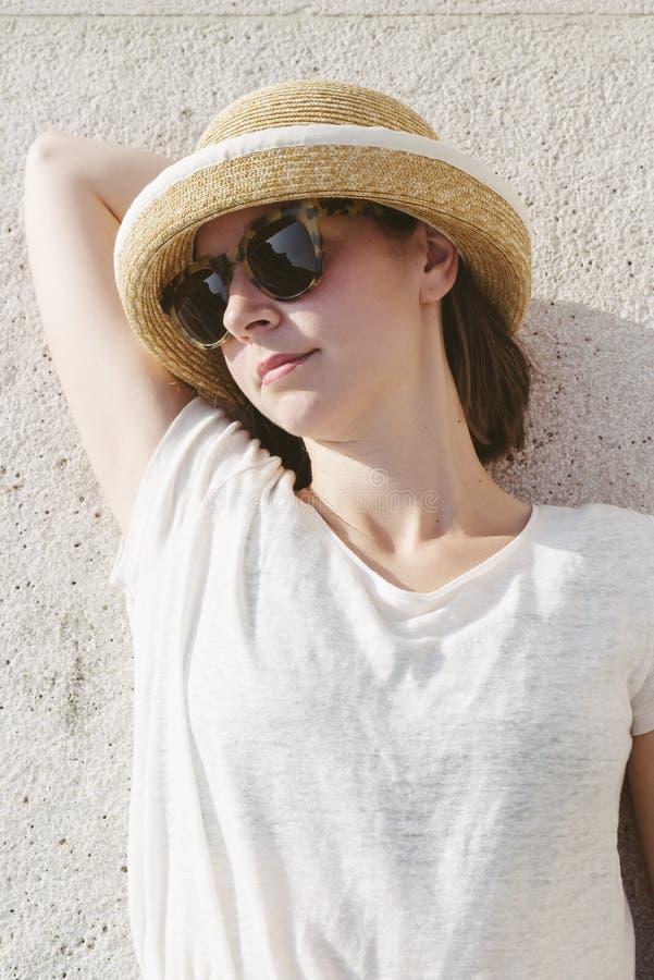 Jong toevallig meisje die een ontspannen hoed en zonnebril dragen stock afbeelding