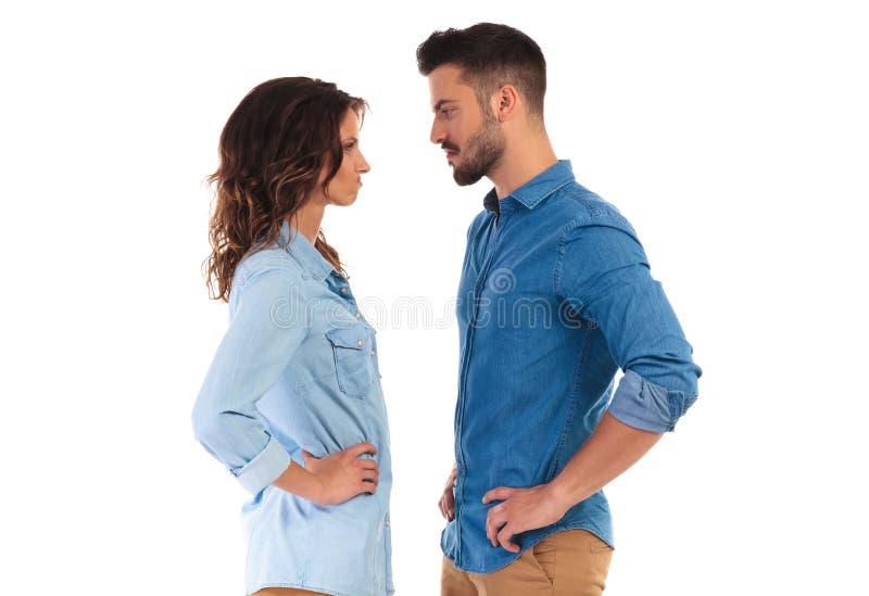 Jong toevallig paar die elkaar onder ogen zien die grappige gezichten maken stock fotografie