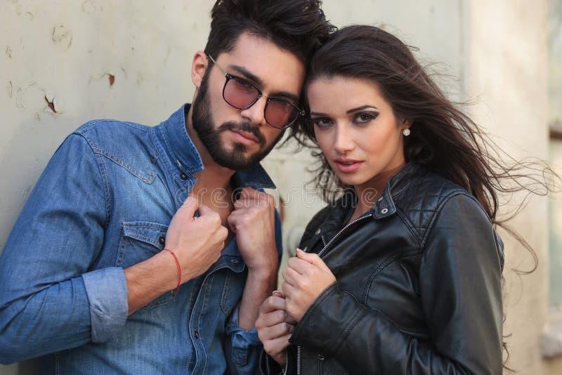 Jong toevallig paar met handen op jasjes stock foto