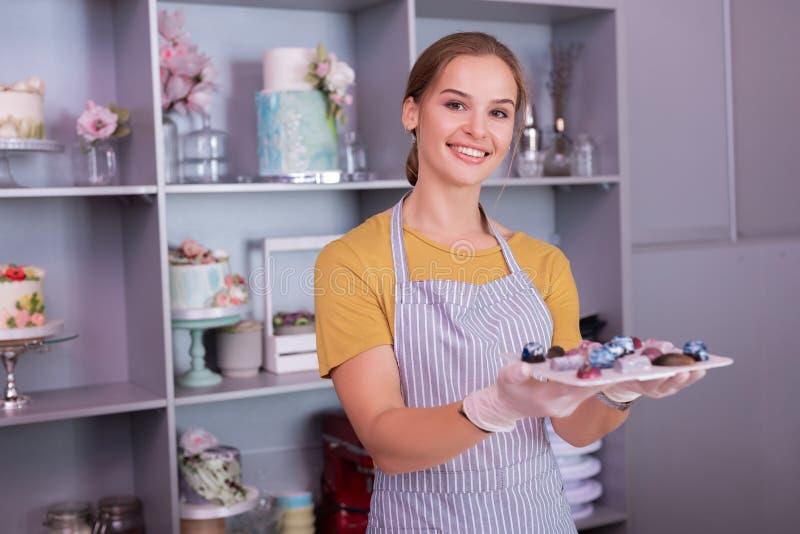 Jong veelbelovend opgewekt chef-kokgevoel het voorstellen van haar geassorteerde chocolade stock foto's