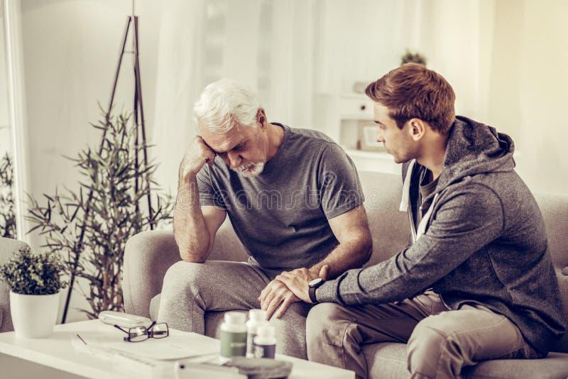 Jong-volwassen kortharige zoon die bejaarde grijs-haired verstoorde vader troosten bij woonkamer royalty-vrije stock fotografie