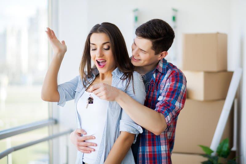 Jong Volwassen Paar binnen Zaal met het Nieuwe Huissleutels van de Dozenholding stock foto's