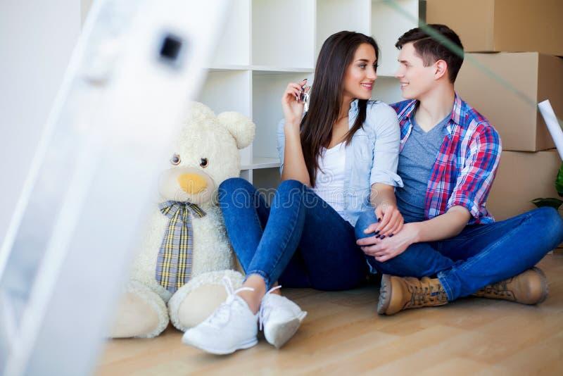 Jong Volwassen Paar binnen Zaal met het Nieuwe Huissleutels van de Dozenholding stock afbeeldingen