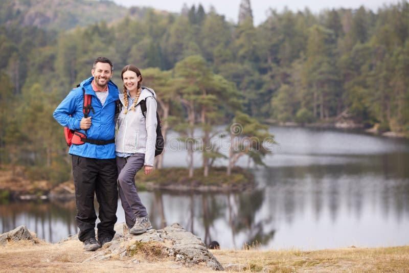 Jong volwassen paar die zich op een rots naast een meer in platteland bevinden, die aan camera, volledige lengte glimlachen stock afbeeldingen