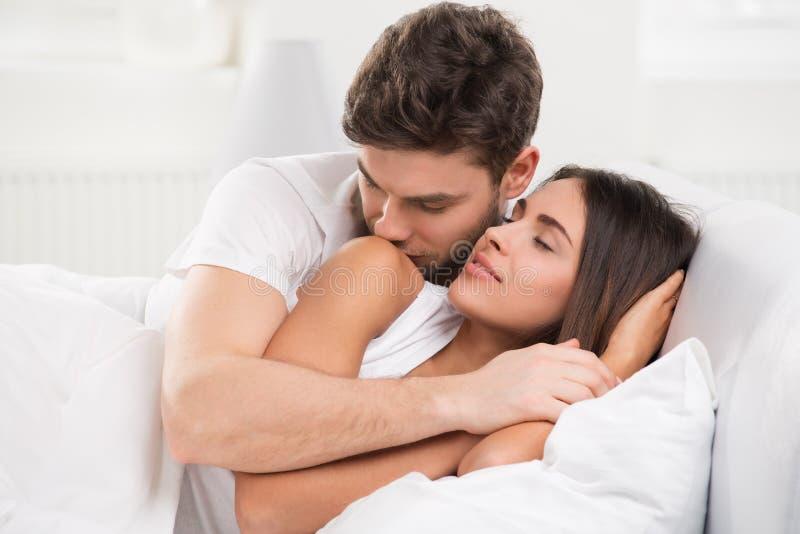 Jong volwassen paar in slaapkamer stock afbeeldingen