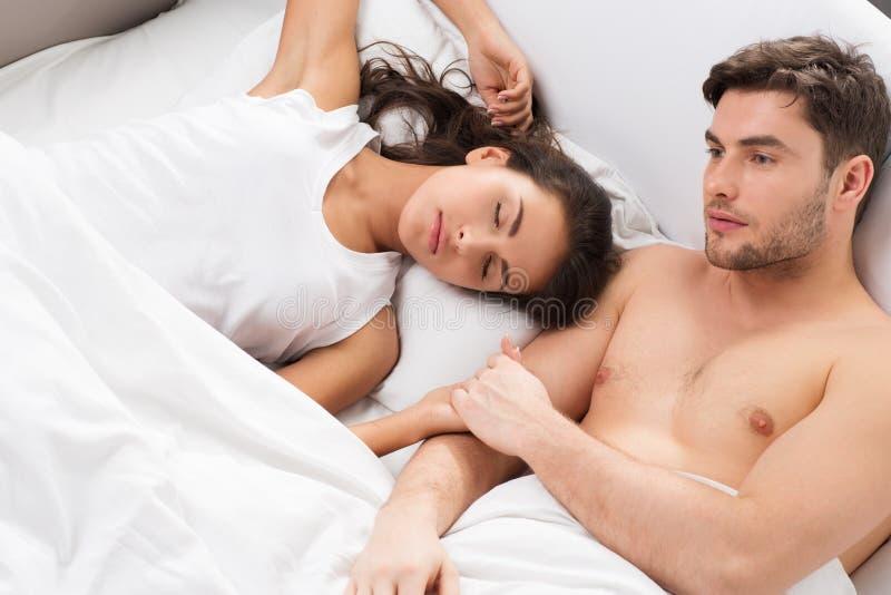 Jong volwassen paar in slaapkamer stock foto