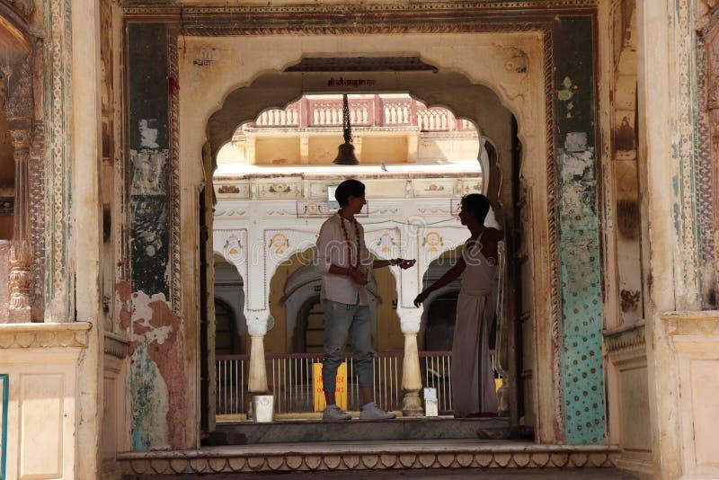 Jong Vreemdelingsmeisje die aan een priester in tempel spreken stock afbeelding