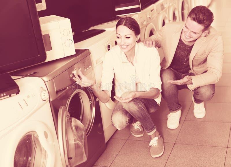 Jong vriendschappelijk paar die wasmachine in hypermarket kiezen royalty-vrije stock foto