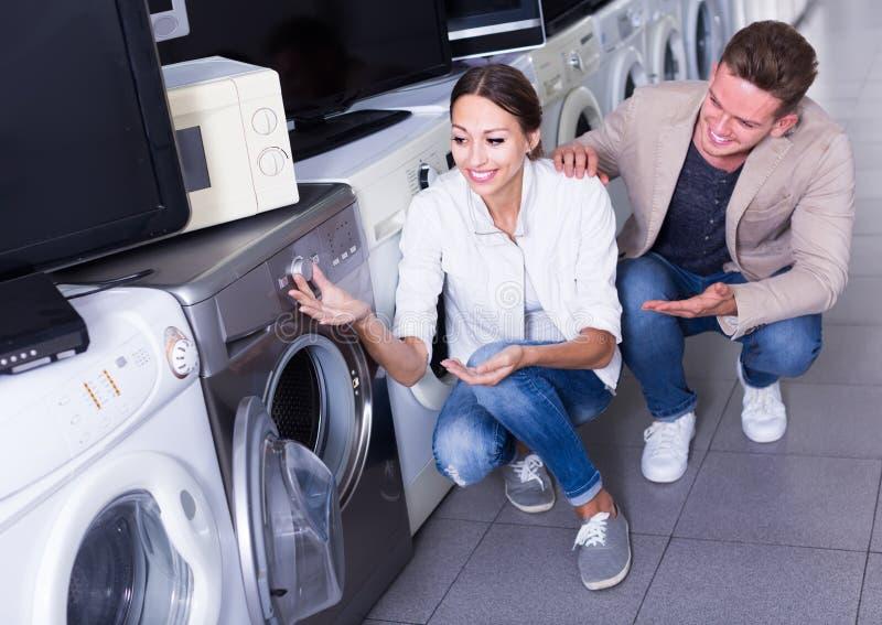 Jong vriendschappelijk paar die wasmachine in hypermarket kiezen royalty-vrije stock foto's
