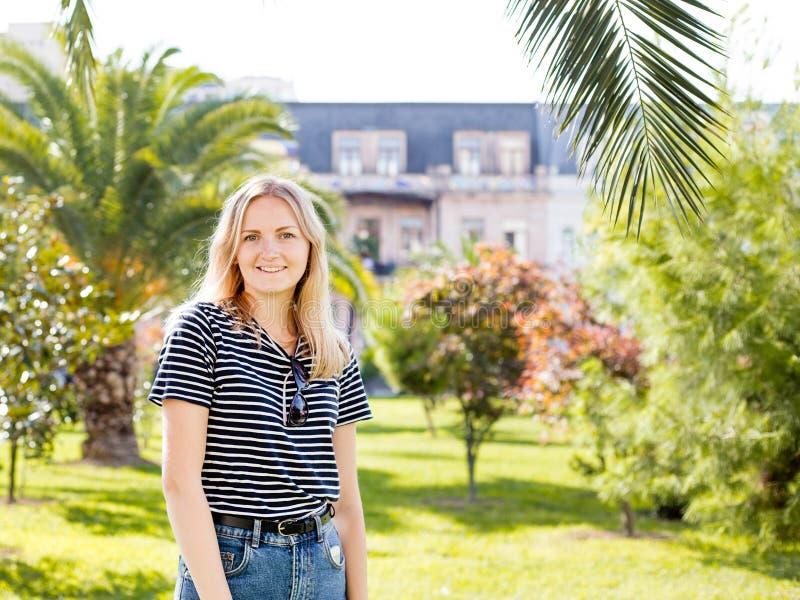 Jong vrij aantrekkelijk wijfje die, op zonnige straat van tropische stad met palmen en geparkeerde auto's lopen, rond kijken die royalty-vrije stock foto's