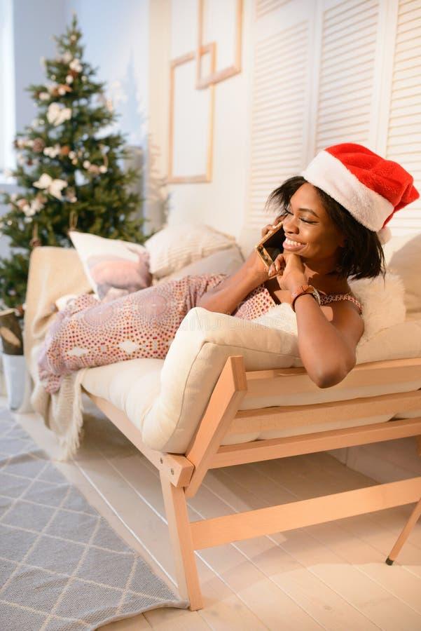 Jong vrij Afrikaans meisje die op de bank liggen en op de telefoon dichtbij de Kerstboom spreken stock afbeelding