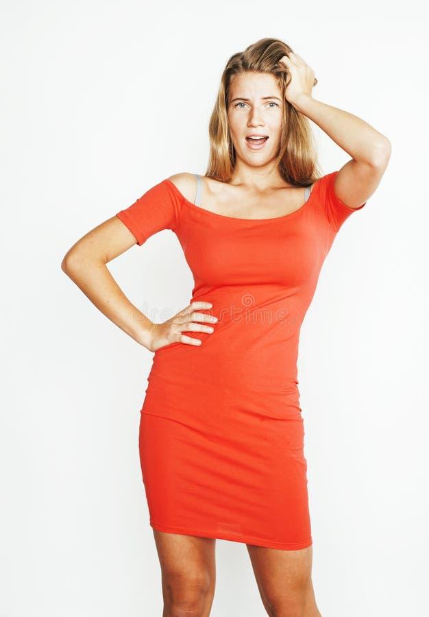 Jong vrij blond meisje in heldere rode kleding die emotioneel stellen die op witte achtergrond, het concept van levensstijlmensen stock afbeeldingen