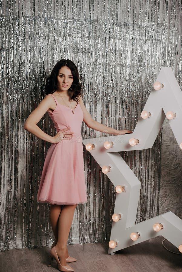 Jong vrij Kaukasisch meisje in een roze kleding op een achtergrond van Kerstmisdecor royalty-vrije stock afbeeldingen
