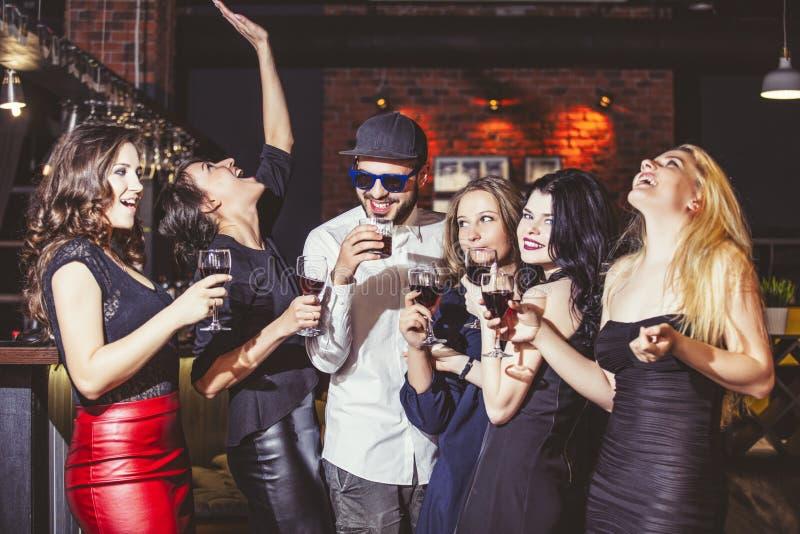 Jong vrolijk bedrijf van vrienden in de clubbar die pretverstand hebben royalty-vrije stock afbeelding