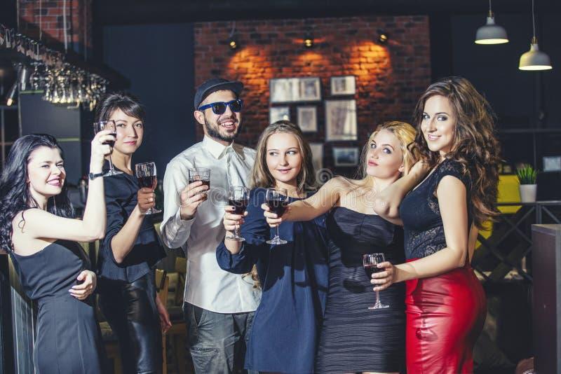 Jong vrolijk bedrijf van vrienden in de clubbar die pretverstand hebben stock afbeelding