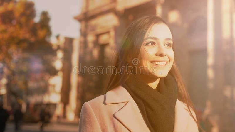 Jong vrolijk gemotiveerd wijfje die dichtbij de universitaire bouw, kansen glimlachen stock foto