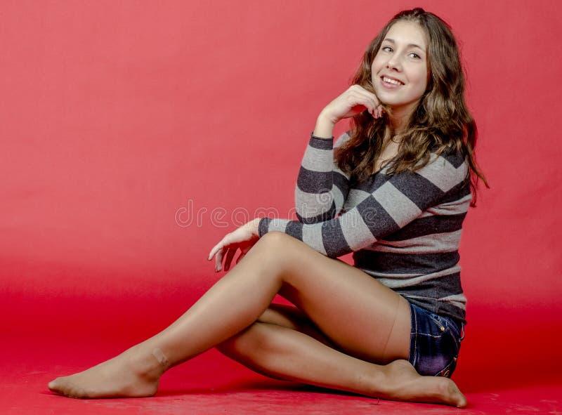 Jong vrolijk meisje in denimborrels en een gestreepte sweater die in de jeugdige stijl lopen stock afbeelding