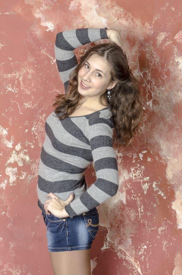Jong vrolijk meisje in denimborrels en een gestreepte sweater die in de jeugdige stijl lopen stock foto
