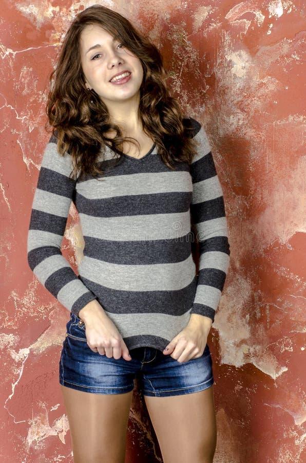 Jong vrolijk meisje in denimborrels en een gestreepte sweater die in de jeugdige stijl lopen stock afbeeldingen