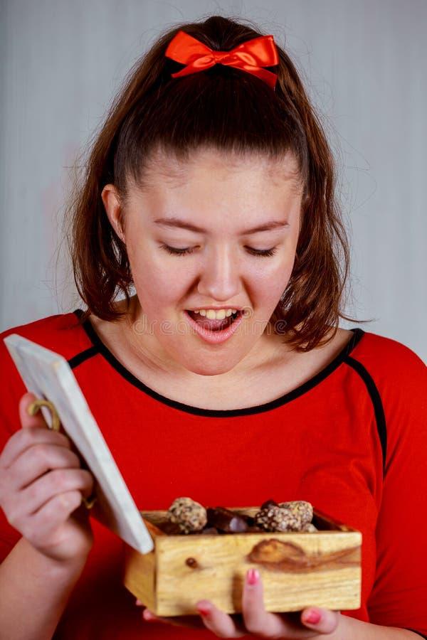 Jong vrolijk meisje in holding het openen doos met chocoladesuikergoed stock fotografie