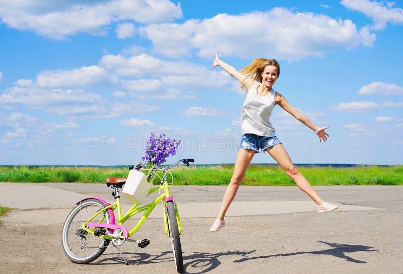 Jong vrolijk meisje met fiets in openlucht stock foto