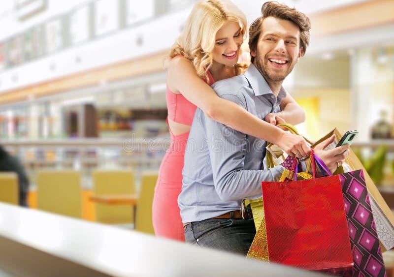 Jong vrolijk paar in het winkelcomplex stock afbeeldingen
