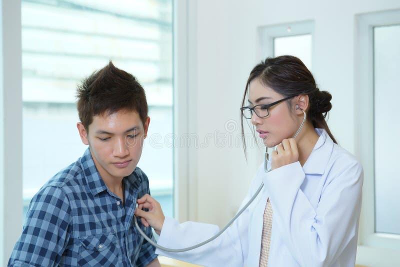 Jong vrouw artsen auscultating mannetje met stethoscoop stock foto's