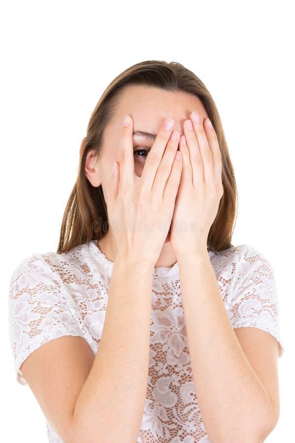 Jong vrouw behandeld sluitend gezicht met handen en het kijken door één oog door haar vingers op witte achtergrond stock afbeeldingen