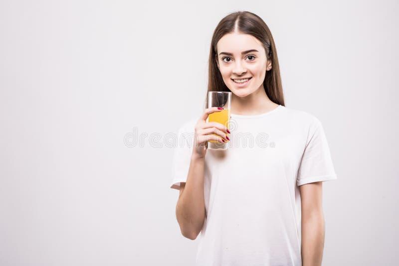 Jong vrouw het drinken jus d'orange Mooi gezicht van vrouwen dichte die omhooggaand met glas jus d'orange op witte achtergrond wo royalty-vrije stock afbeelding