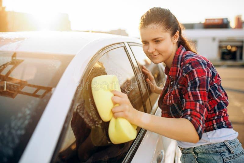 Jong vrouw het schrobben voertuigglas met schuim stock afbeeldingen