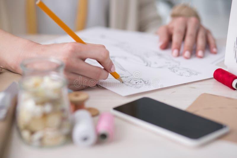 Jong vrouwelijk meer couturier het schetsen nieuw kledingstuk stock afbeeldingen
