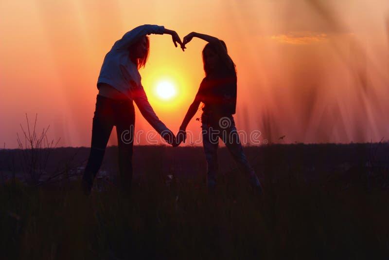 Jong Vrouwelijk Paar die Hartvorm met Handen maken bij Zonsondergang De abstracte Achtergrond van de Liefde Mensen, Liefde, Vrien royalty-vrije stock foto's