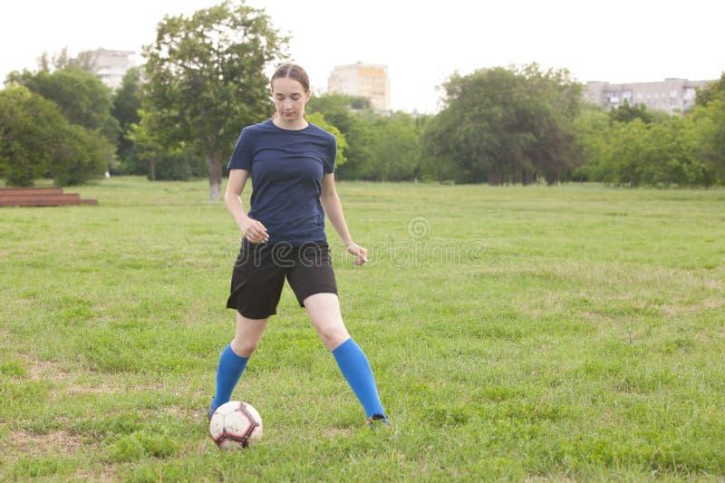 Jong vrouwelijk voetbal of voetbalster die met lang haar in sportwear en laarzen bal voor het doel in sprong schoppen bij het sta stock afbeelding