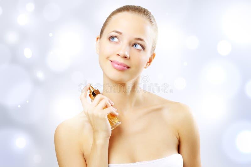 Jong vrouwen bespuitend parfum stock foto